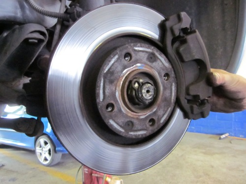 A Century Autocare mechanic checks the brake calipers